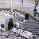 Sistema stampa e applica per applicazione etichetta su due lati di una scatola in movimento