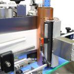 Dispositivo per applicazione fronte e retro su contenitori cilindrici