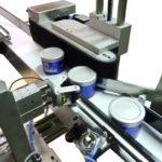 Dispositivo rotazione con rulli di contrasto integrato su sistema di etichettatura con rotolatore continuo