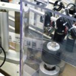 Dispositivo rotazione con rulli di contrasto integrato su sistema di etichettatura con rotolatore continuo per alte velocità