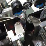 Dispositivo applicazione fronte e retro su bottiglie e falconi cilindrici